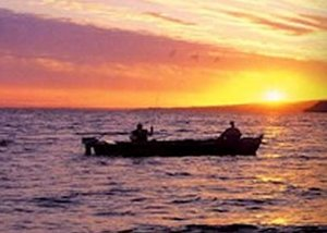 Anglers in Sheephaven Bay give a friendly wave to evening golfers
